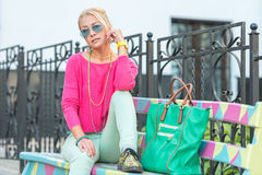 Street fashion beautiful woman sitting on a bench Royalty Free Stock Image