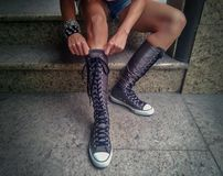 Street fashion. Boots, sneakers with long laces on a girl with metal and leather bracelets Royalty Free Stock Image