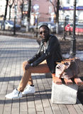 Street fashion concept african man with bag sits on a bench in city park Royalty Free Stock Photo