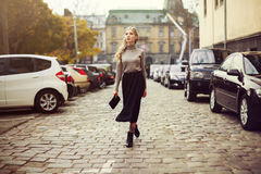 Street fashion concept: full body portrait of young beautiful woman walking in the city. Model looking aside. Toned and Royalty Free Stock Photo