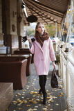 Street fashion concept: full body portrait of young beautiful woman wearing pink coat with handbag walking in the city Royalty Free Stock Photography