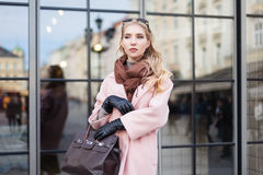 Street fashion concept: portrait of young beautiful woman wearing pink coat with handbag posing at the glass door. City Stock Photos
