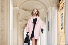 Street fashion concept: portrait of young beautiful woman wearing pink coat with handbag walking in the city. Model Royalty Free Stock Images