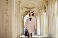 Street fashion concept: portrait of young beautiful woman wearing pink coat with handbag walking in the city. Old Royalty Free Stock Image