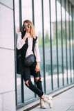 Street fashion concept - pretty young slim woman in rock black style posing against the wall Royalty Free Stock Photography