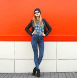 Street fashion concept - stylish hipster woman in rock. Black style posing against a colorful urban wall Royalty Free Stock Images