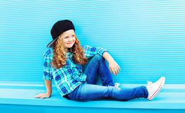 Street fashion concept - stylish kid little girl with curly hair. On a blue background Stock Images