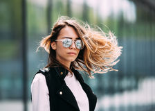 Street fashion concept. Young beautiful model in the city. Beautiful blonde woman wearing sunglasses. Close-up portrait of a young sexy girl hipster Royalty Free Stock Photos