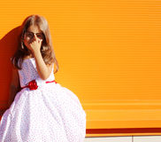 Street fashion little girl in dress. Near colorful wall Stock Photography