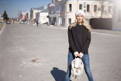 Street fashion look. Beautiful girl in black hoody. Street fashion look. Beautiful girl wearing white hat, black hoody, jeans and beige backpack in the city royalty free stock photos