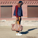 Street fashion look concept stylish african young man wearing vest jacket, sweater, bag walking in city evening, vintage colors royalty free stock photos