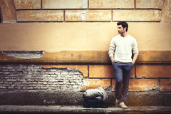 Street fashion model tourist man outdoor. Waiting on grunge wall. A beautiful model man waiting leaning against an old wall. Vintage scene, old ruined wall. On Stock Image
