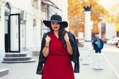 Street fashion, plus size model. Young stylish woman wearing red maxi dress, black leather jacket and hat walking on the city street in autumn. Fall fashion Royalty Free Stock Photo