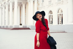 Street fashion, plus size model. Young stylish woman wearing red maxi dress, black leather jacket and hat walking on the city street in autumn. Fall fashion Stock Photos