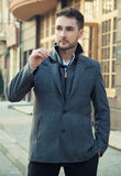 Street fashion.Portrait of handsome man in trendy casual coat an. D sun glasses Stock Photos