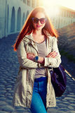 Street fashion portrait of young foxy-haired woman in a jeans and violet sunglasses with a leather handbag against the Royalty Free Stock Images