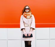 Street fashion pretty stylish woman model in coat and sunglasses. With bag clutch posing outdoors against colorful wall in the city Royalty Free Stock Images