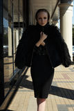 Street fashion style. Beautiful model in chic warm jacket with fluffy fur. High fashion portrait of beautiful sexual woman model in black chic warm jacket with Stock Image