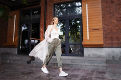 Free Street Fashion Style. Beautiful Sexy Woman Wearing Fashionable Spring Or Autumn Clothes, Beige Trench Coat, Cargo Pants, Royalty Free Stock Photo - 159317575