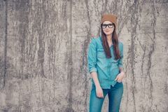 Street fashion, style, youth, swag, denim concept. Female modelm. Is in fashionable jeans outfit, posing on the concrete wall`s background outside Royalty Free Stock Images