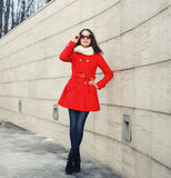 Street fashion, stylish woman in red jacket. On against a wall stock image