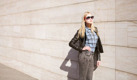 Street fashion, stylish young girl in leather jacket. And sunglasses in the city royalty free stock images