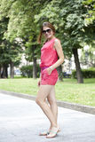 Street fashion. Young woman in red shorts and a blouse Royalty Free Stock Photo