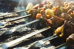 Street fast food festival, beef and chicken kebab at grill. Street fast food festival. Cooking raw kebab on metal skewer. BBQ fresh beef chop slices. Traditional royalty free stock photos