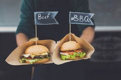 Street fast food festival hamburgers with beef and bbq. Street fast food festival, hamburgers cooked at barbecue outdoors. Cookout american bbq food, closeup in royalty free stock photography