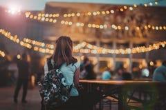 Street festival in Tirana, European capital. Tirana, Albania. September 17, 2017: Young girl with backpack enjoying illuminated city center. Evening in Tirana Royalty Free Stock Photography