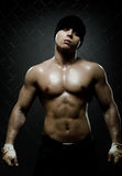 Street fighter. Vertical photo  muscular young  guy street-fighter,  aggression look, hard light Royalty Free Stock Photos