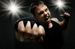 Street-fighter. Horizontal photo  muscular young  guy street-fighter, cuff  fist close up on camera and yell , hard light Royalty Free Stock Images