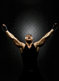 Street fighter. Vertrical photo  muscular young  guy street-fighter,  triumphant cries  yell , hard light Royalty Free Stock Photo