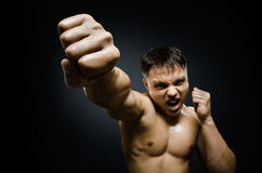 Street-fighter. Horizontal photo  muscular young  guy street-fighter, cuff  fist close up on camera and yell , hard light Royalty Free Stock Photos
