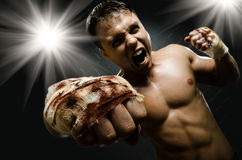 Street fighter. Horizontal  photo  muscular young  guy street-fighter, cuff  fist close up on camera and yell , hard light Royalty Free Stock Image