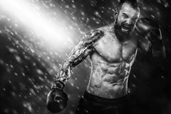 Sportsman muay thai boxer fighting on black background with smoke. Copy Space. Sport concept. Street fighter fighting in boxing cage. Background with lights and stock image
