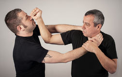Street fighting self defense technique against holds and grabs. Kapap instructor demonstrates street fighting self defense technique against holds and grabs with stock photo