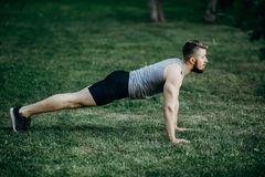 Young fit muscular man doing plank outdoors stock photos