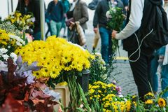 Small business. Street flower shop. In the foreground there are beautiful yellow and other flowers. The guy is holding a. Street flower shop. In the foreground stock photos