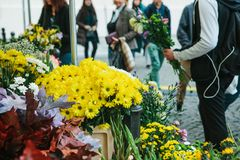 Street flower shop. In the foreground there are beautiful yellow and other flowers. The guy is holding a bouquet of. Flowers and is going to give them to his stock photos