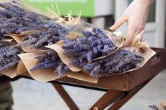 Street flower shop stall, hand holding a bouquet of lavender. Street flower shop stall, hand holding a wrapped bouquet of lavender stock photo
