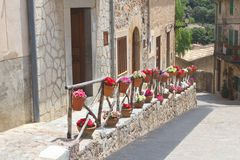 Scenic and rustic street with flowerpots in Valldemossa, Majorca. Scenic and rustic street with flowerpots and blooming flowers in Valldemossa, Mallorca (Majorca Royalty Free Stock Photography