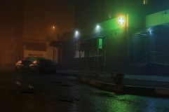 Street with fog and green pharmacie cross royalty free stock image