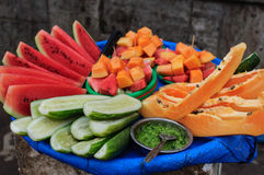 Street food in Asia. Fruits of papaya, watermelon and cucumber with spicy chutney Stock Images