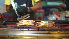 Street food asia, traditional Asian dishes. seafood shrimp on the grill, the cook toast their burner. night food market