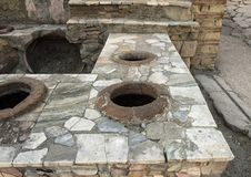 Street food bar with pots to keep food hot in the remains of Herculaneum Parco Archeologico di Ercolano. Pictured is a street food bar with pots to keep food hot Royalty Free Stock Photography
