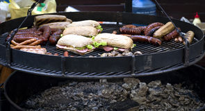 Street food, barbecue, meat, cooked on the grill. Street food, barbecue, meat, sausages and sandwiches cooked on the grill stock photography