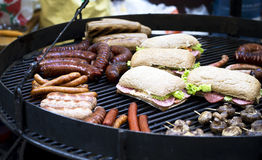 Street food, barbecue, meat, cooked on the grill. Street food, barbecue, meat, sausages and sandwiches cooked on the grill stock image