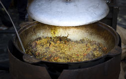 Street food, barbeque pilaf. Pilaf cooked in a cauldron royalty free stock photo