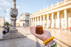 Street food in Bordeaux. Holding a traditional Bordeaux sweet cake called Canele outdoors on the street near the Grand theatre building in Bordeaux royalty free stock photo